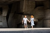 happy redhead couple holding hands running at city street