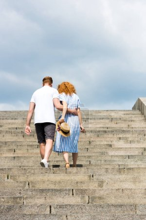 rear view of man embracing redhead girlfriend and walking on stairs