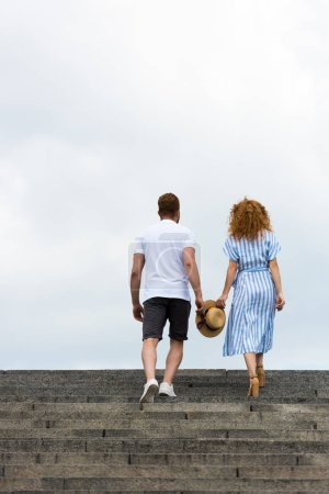 Photo for Rear view of couple holding straw hat and walking on stairs against cloudy sky - Royalty Free Image