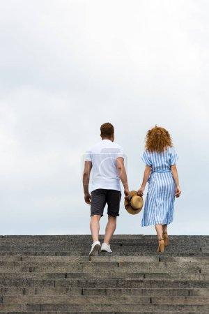 Foto de Vista trasera del par sosteniendo el sombrero de paja y caminar en las escaleras contra el cielo nublado - Imagen libre de derechos