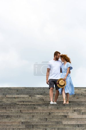 Photo for Redhead man embracing girlfriend and walking on stairs against cloudy sky - Royalty Free Image