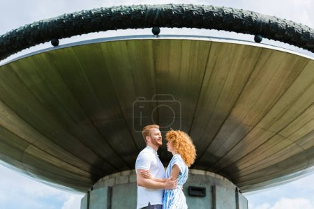 redhead couple embracing each other in front of modern building