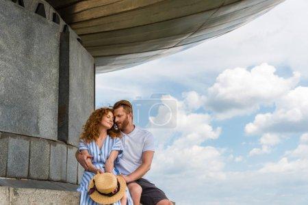 redhead couple sitting near building against blue cloudy sky