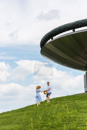 distant view of redhead couple on grassy hill near modern building