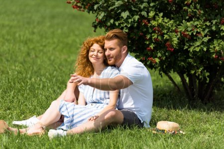 Photo for Smiling redhead man pointing by hand to girlfriend on grass in park - Royalty Free Image