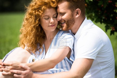 selective focus of smiling redhead couple sitting outdoors