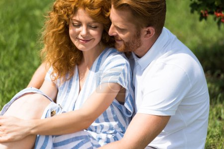 happy redhead man embracing girlfriend on grass outdoors