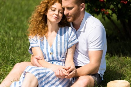 redhead couple with closed eyes sitting on grass in park