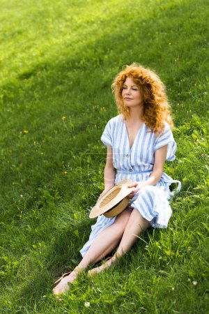 Photo for Redhead attractive woman with straw hat in hands sitting on grassy meadow - Royalty Free Image