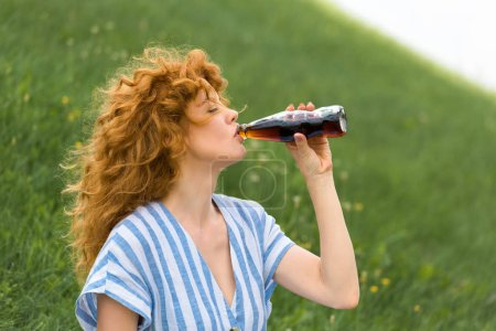 Photo for Side view of beautiful redhead woman drinking soda outdoors - Royalty Free Image