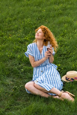 smiling redhead woman sitting on grassy meadow with soda