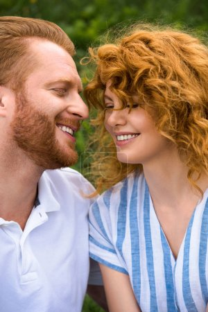 portrait of happy redhead couple with closed eyes outdoors