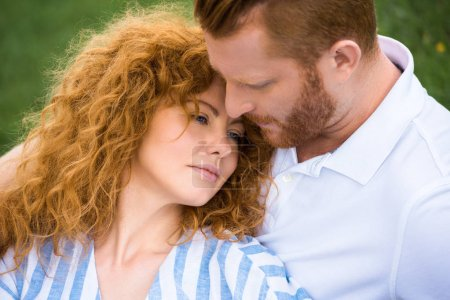 attractive redhead woman laying on boyfriend shoulder