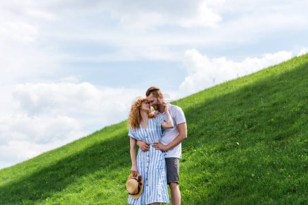 redhead couple embracing each other on green hill