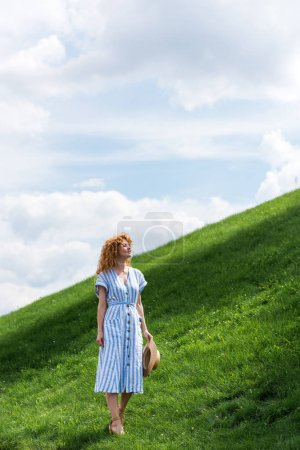 Photo for Smiling beautiful redhead woman in straw hat on grassy hill - Royalty Free Image