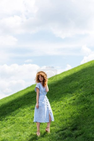 smiling redhead woman posing with straw hat on grassy hill against blue sky