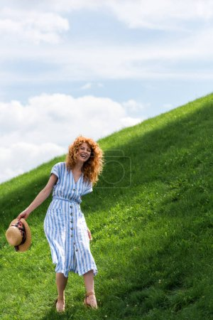 Photo for Happy beautiful redhead woman with straw hat in hand standing on grassy hill against blue sky - Royalty Free Image
