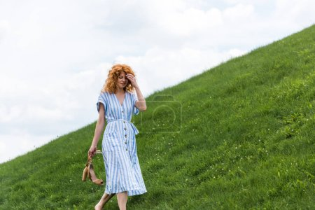 Photo for Attractive redhead woman carrying shoes on grassy hill - Royalty Free Image