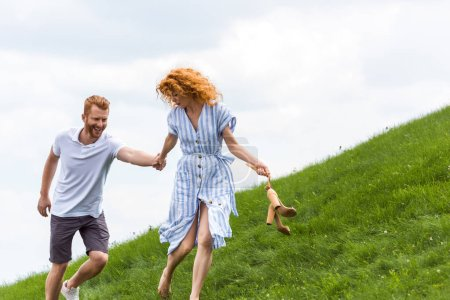 smiling redhead couple holding hands and running on grassy hill