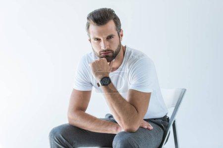 modisch gut aussehender Mann in weißem T-Shirt mit Armbanduhr auf Stuhl sitzend, isoliert auf weißem