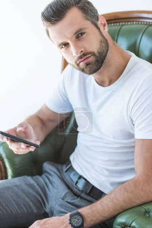 elegant bearded man using smartphone while sitting in armchair, isolated on white