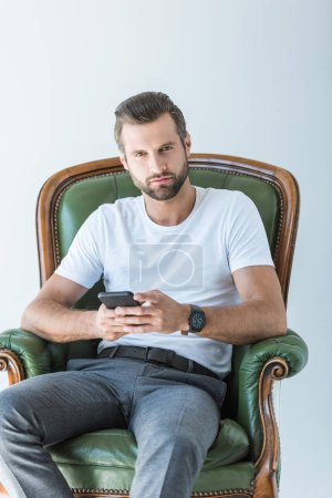 thoughtful bearded man using smartphone while sitting in armchair, isolated on white