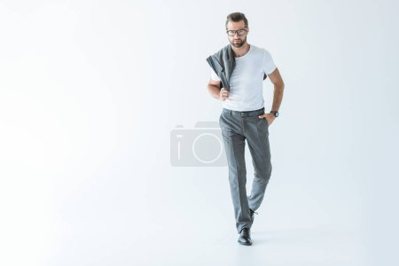 handsome stylish man posing in white t-shirt with gray jacket on shoulder, isolated on white