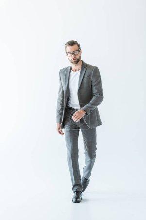 Photo pour Élégant homme d'affaires élégant marchant en costume gris, isolé sur blanc - image libre de droit