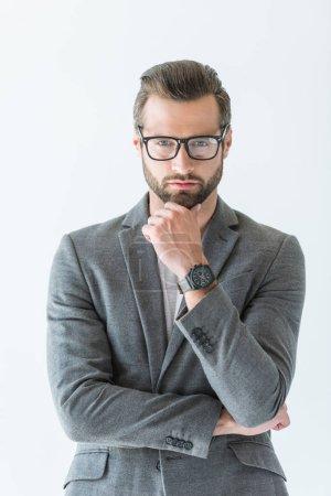 Photo pour Homme d'affaires réfléchi dans des lunettes et costume gris avec montre-bracelet à portée de main, isolé sur blanc - image libre de droit
