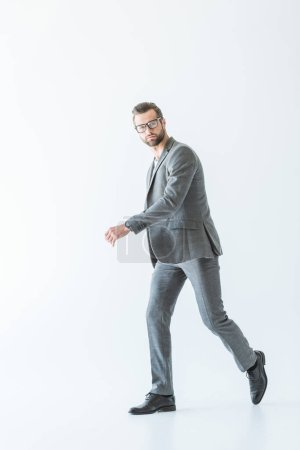 stylish businessman walking in gray formal wear, isolated on white