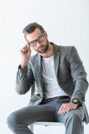 Photo pour Bel homme d'affaires confiant en costume gris, assis sur la chaise, isolé sur blanc - image libre de droit
