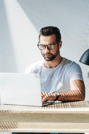 handsome brunet man working with laptop