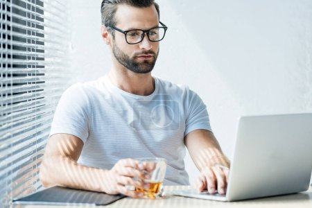 brunet man holding glass of whiskey and working with laptop