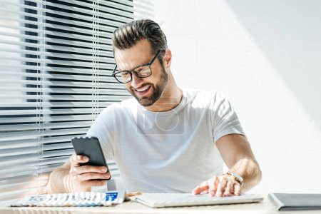 smiling man using smartphone while sitting at workplace