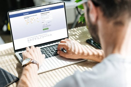 Photo for Partial view of man using laptop with facebook website on screen - Royalty Free Image