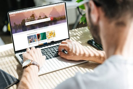 Photo for Back view of man using laptop with shutterstock website on screen - Royalty Free Image