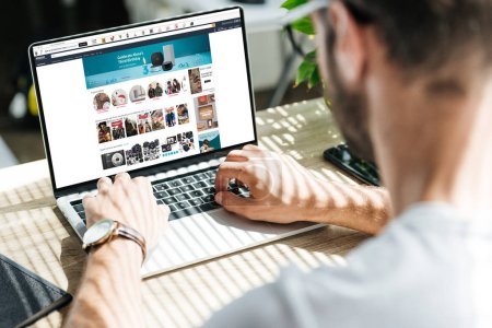 Photo for Back view of man using laptop with amazon website on screen - Royalty Free Image
