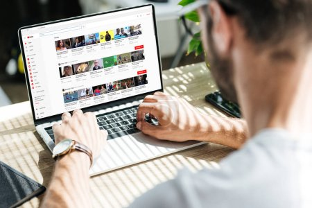 Photo for Back view of man using laptop with youtube website on screen - Royalty Free Image