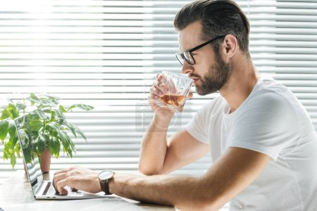 Photo for Handsome bearded man drinking whiskey while using laptop at workplace - Royalty Free Image