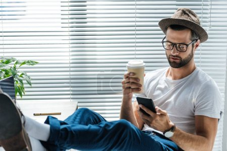 bearded man in hat holding coffee to go and using smartphone