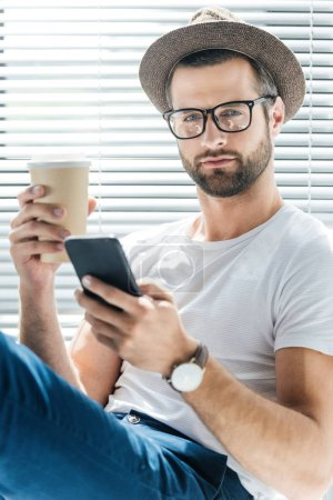 handsome man in eyeglasses and hat holding coffee to go and using smartphone