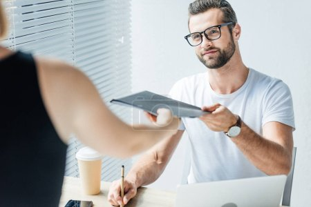 handsome businessman giving documents to colleague in modern office