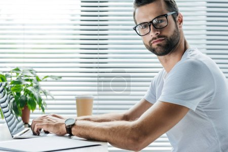 bearded man using laptop while sitting at workplace with disposable cup of coffee