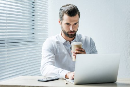 Photo for Handsome focused businessman holding coffee to go while working with laptop in office - Royalty Free Image