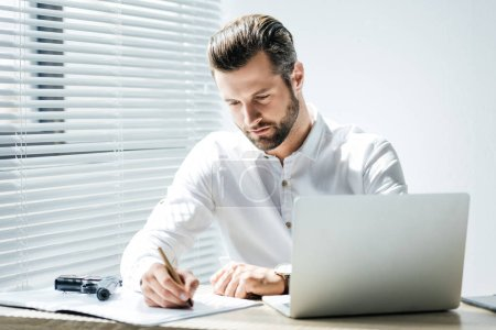concentrated businessman writing in documents while sitting at workplace with laptop and gun
