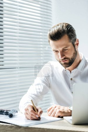 handsome focused businessman doing paperwork at workplace with laptop and gun