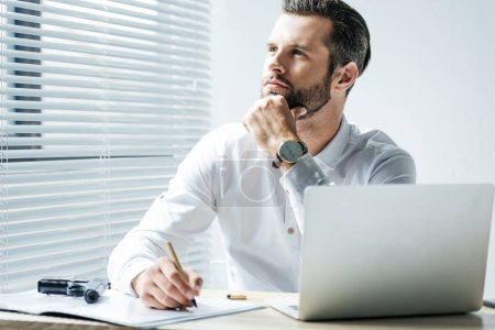 pensive businessman doing paperwork in office with laptop and gun