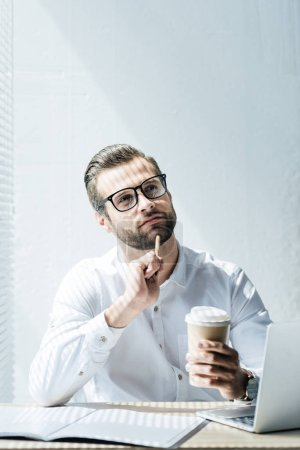 thoughtful businessman sitting at workplace with laptop, paperwork and disposable cup of coffee
