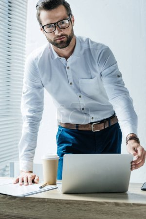 Photo for Handsome bearded businessman in office with laptop and coffee to go - Royalty Free Image