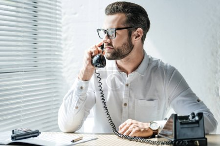 bearded businessman talking on rotary telephone at workplace with weapon
